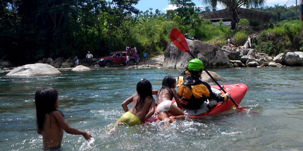 Laughing Ecuadorian girls hanging on back of kayak