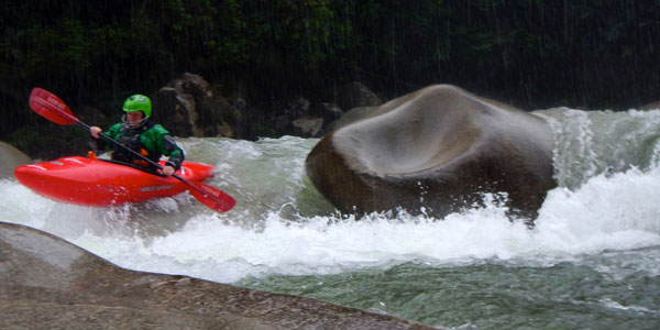 A kayaker with a football style facemask boofs a drop.