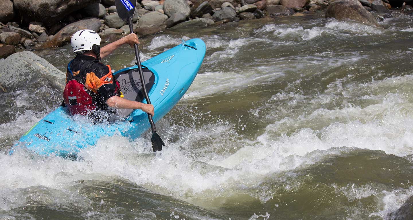 A blue kayak executes a boot with lots of air