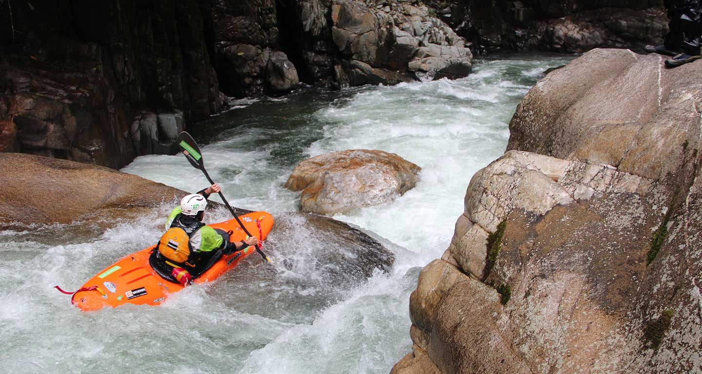 An orange kayak races downstream through some difficult whitewater