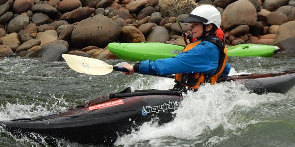 A woman kayak surfing a wave.
