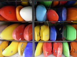 Dozens of colorful kayaks stored in shed.